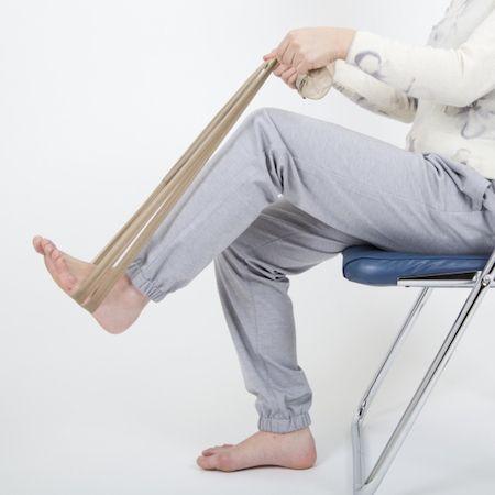 パンストを結んでチューブ状にし、両手で持って、足の裏に通す。イスに座ったまま、グッと踏み込む。この状態をキープするだけでも、腰まわりの筋肉を鍛えられる。