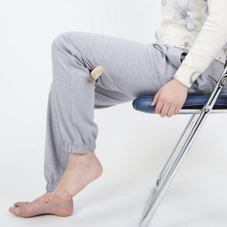 【1】足を上げて、すりこぎをひざの裏に挟み、落とさないようにする。この状態をキープするだけでOK! これだけでもヒップアップにつながるエクササイズ効果が期待できる。