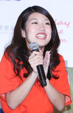 オレンジの服を着てマイクを持ちながら拍手をする芸人、横澤夏子