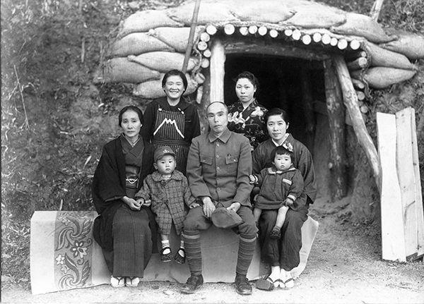 【写真】婚家の裏の防空壕前で。手前の義父母の間に座るのが勝彦さん、ツチヱさんは長女の洋子さんをひざにのせて